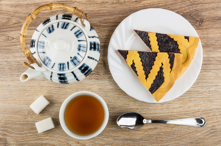 Pieces of bilberry pie in plate, teapot, cup of tea, lumpy sugar and teaspoon on wooden table. Top view