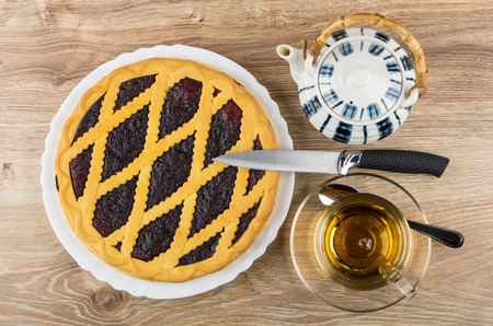 Bilberry pie in white dish, teapot, knife and tea in cup on wooden table. Top view
