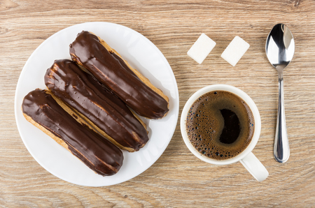 Eclairs with chocolate in plate, coffee in cup, lumpy sugar and spoon on wooden table. Top view