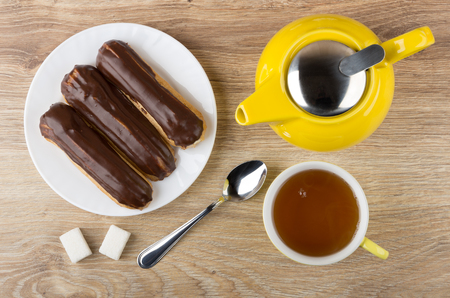 Eclairs with chocolate in plate, yellow teapot, tea in cup, lumpy sugar and spoon on wooden table. Top view Stock Photo