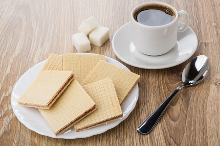 Heap of waffles in white plate, lumpy sugar, black coffee and spoon on wooden table Stock Photo