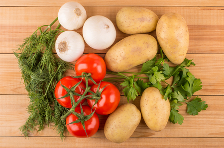 white washed: Heap of raw washed potatoes, white onion, red tomatoes, parsley and dill on wooden table. Top view Stock Photo