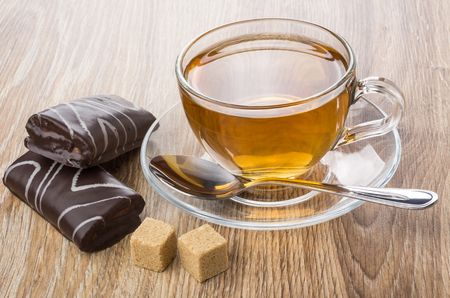 Small chocolate swiss rolls, transparent cup with tea, lumpy sugar and teaspoon on wooden table Stock Photo