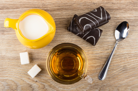 Jug of milk, chocolate swiss rolls, cup with tea, lumpy sugar, teaspoon on wooden table. Top view Stock Photo