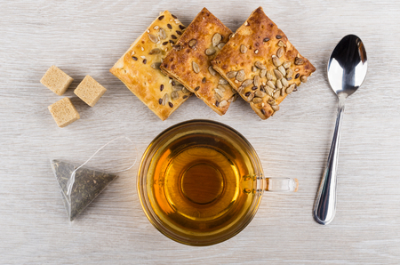 Cup of tea, sugar, teabag and cookies with sunflower seeds and sesame on wooden table. Top view Stock Photo