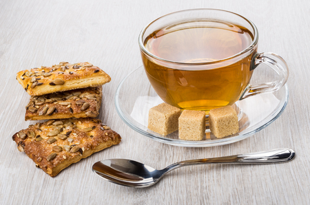 Cookies with sunflower seeds and sesame, sugar, teaspoon and tea on wooden table Stock Photo