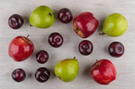 Apples, pears and plums scattered on wooden table. Top view