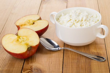 White bowl with cottage cheese, pieces of apple and spoon on wooden table