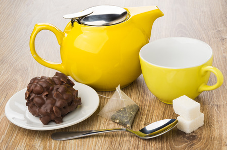 Cookie with chocolate and nuts, teapot, cup, teabag, sugar and teaspoon on wooden table