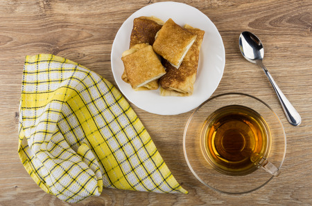 checker: Pancakes with cottage cheese in plate, cup of tea, napkin, spoon on wooden table. Top view Stock Photo