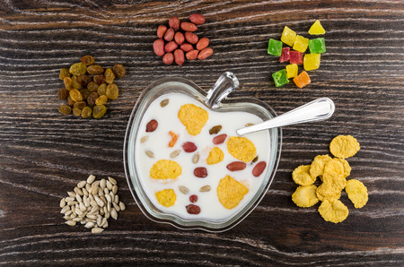 Heap of different ingredients for muesli and yogurt in transparent bowl on wooden table. Top view Stock Photo