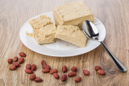 Scattered peanuts, broken peanut halva in white plate, teaspoon on wooden table