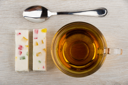 pastila: Two pieces of pastila with marmalade, teaspoon and tea in transparent cup on wooden table. Top view Stock Photo