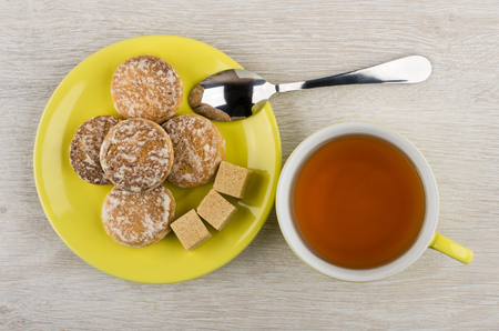 Honey-cake, lumpy sugar in saucer, teaspoon, cup of tea on wooden table. Top view Stock Photo