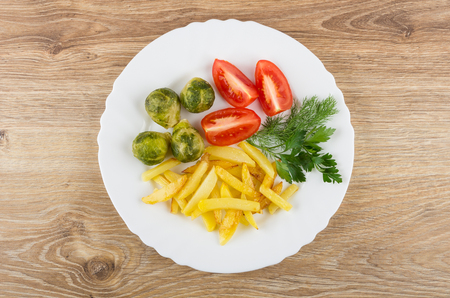 table top: White dish with fried potatoes, tomatoes, brussels sprouts and greens on wooden table. Top view