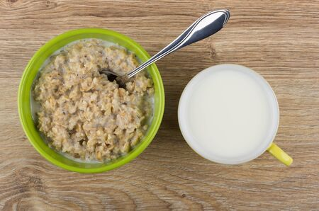 table top: Porridge from oat flakes with milk in bowl, spoon and cup of milk on wooden table. Top view