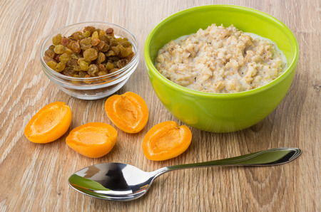 Porridge from oat flakes with milk in bowl, raisins, apricot and spoon on wooden table