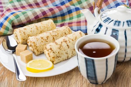 Pancakes with stuffed, lemon, sugar, teapot, tea and napkin Stock Photo