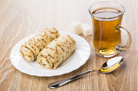 Two pancakes with stuffed in plate, sugar, cup of tea and teaspoon on wooden table