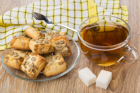 Cup of tea, lumpy sugar, plate with cookies, napkin and teaspoon on wooden table