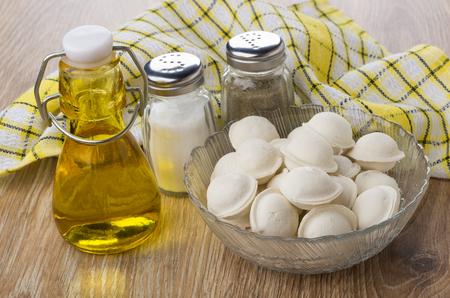 Frozen dumplings in bowl, salt, pepper and vegetable oil on wooden table Stock Photo