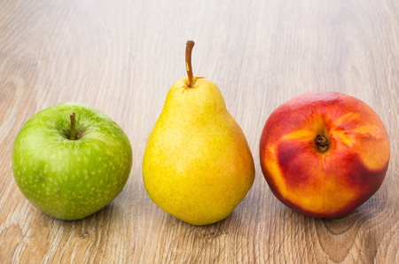 Row of green apple, yellow pear and nectarine on wooden table