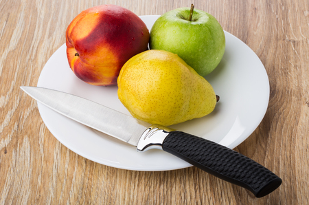 Nectarine, pear, apple and kitchen knife in white plate on wooden table