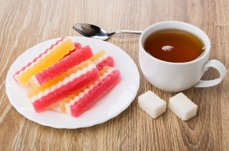 Multicolored marmalade in white plate, cup of tea, lumpy sugar and teaspoon on wooden table