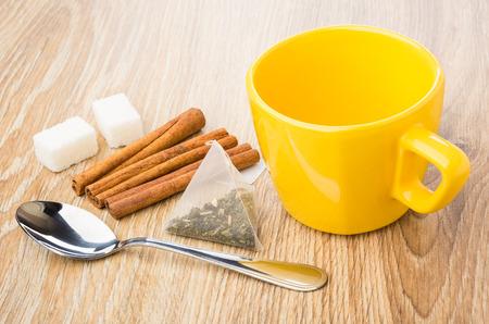 Empty cup, cinnamon sticks, teaspoon, tea bag, lumpy sugar on wooden table Stock Photo