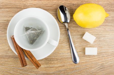 Tea bag in cup, cinnamon sicks on saucer, lemon, lumpy sugar, teaspoon on wooden table. Top view