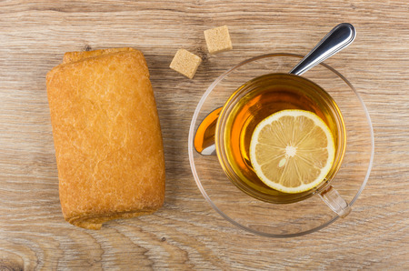 Puff pie with stuffed and cup of tea with lemon on wooden table. Top view Stock Photo