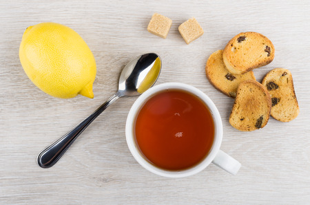 Rusks with raisin, cup of tea, lemon, lumpy sugar and teaspoon on wooden table. Top view