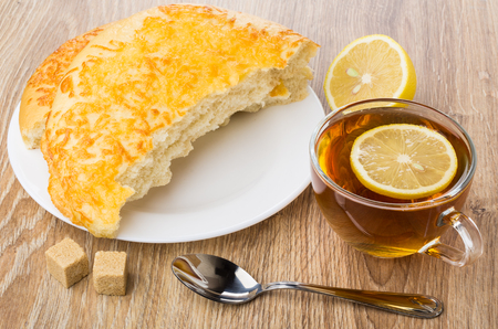 Tea with lemon, broken flat bread with cheese, sugar and teaspoon on wooden table Stock Photo