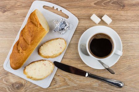 Sandwiches with melted cheese, loaf of bread on cutting board, black coffee, sugar, knife and spoon on wooden table. Top view Stock Photo
