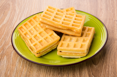 Heap of waffles in green plate on wooden table