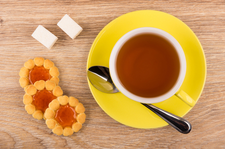 Cookies with jam, cup of tea, sugar and spoon on wooden table. Top view Stock Photo