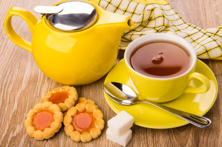 Cookies with jam, teapot, cup of tea, sugar and spoon on wooden table