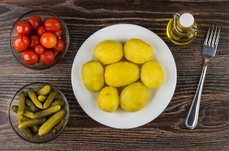 marinated gherkins: Baked potatoes in plate, bowls with marinated gherkins and tomatoes, bottle of oil and fork on wooden table. Top view