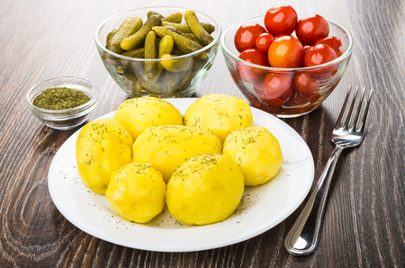marinated gherkins: Baked potatoes in plate, bowls with marinated gherkins, tomatoes, dry dill and fork on wooden table