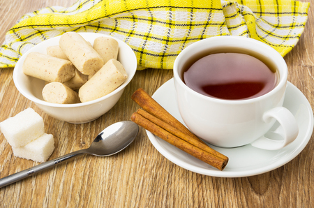 Creamy candy bars in bowl, cup of tea, cinnamon, sugar and teaspoon on wooden table Stock Photo
