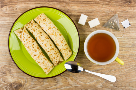 Pancakes with stuffed in green plate, cup of tea, lumpy sugar, tea bag and teaspoon on wooden table. Top view Stock Photo