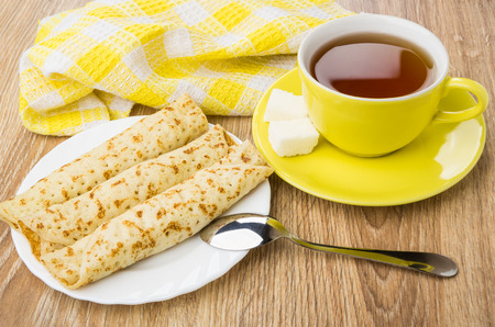 Yellow cup with tea and sugar on saucer, plate of pancakes with stuffed and teaspoon on wooden table Stock Photo