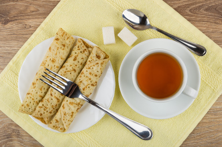Cup of tea, pancakes with stuffed, sugar, teaspoon and fork on yellow napkin. Top view