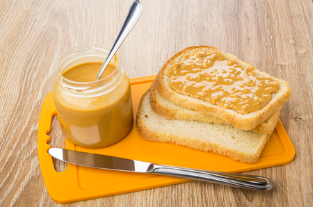 Bread, sandwich with peanut butter, jar on cutting board, knife on wooden table Stock Photo