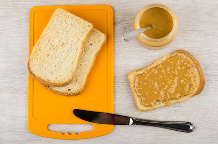 Sandwich with peanut butter, bread on cutting board, jar with butter and teaspoon, knife on wooden table. Top view Stock Photo