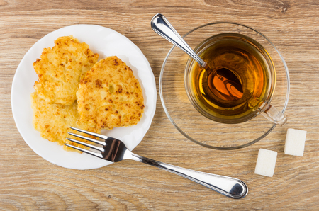 Cottage cheese pancakes in plate, cup of tea, sugar and fork on wooden table. Top view