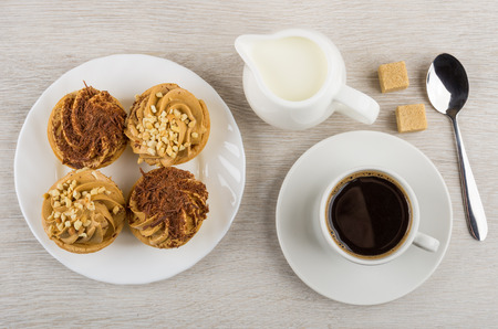 Tartlets with cream, chocolate, nut, milk, black coffee, spoon and sugar on wooden table. Top view
