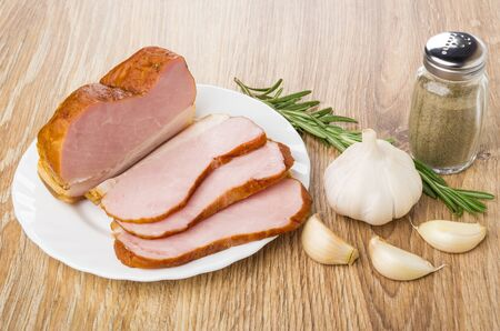 Slices of smoked gammon in plate, rosemary, pepper, and garlic on wooden table Stock Photo