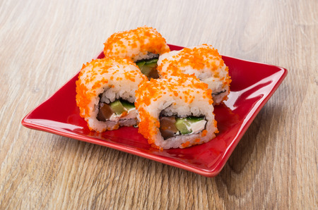 Rolls with flying fish roe in red bowl on wooden table