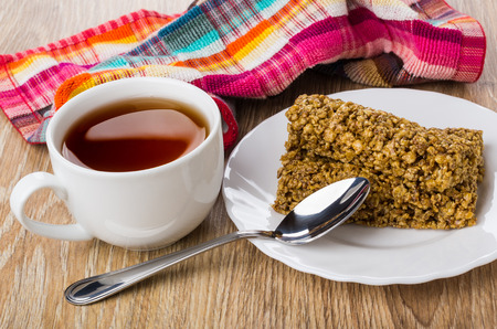 Granola bar in plate, tea in cup, teaspoon, checkered napkin on wooden table